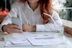 Selektiv fokus på händer av den smarta telefonen för attraktiv ung asiatisk mobil för affärskvinna hållande och analyseringsdiagr arkivbild