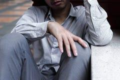 Selektiv fokus på händer av frustrerat stressat ungt asiatiskt sammanträde för affärsman på golvet royaltyfri bild