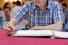 Selektiv fokus på händer av ung gästmanhandstil på minnesboken för att välsigna ord för att ansa och bruden i bröllopceremoni Royaltyfri Fotografi