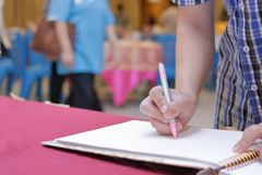 Selektiv fokus på händer av ung gästmanhandstil på minnesboken för att välsigna ord för att ansa och bruden i bröllopceremoni Fotografering för Bildbyråer