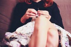 Selektiv fokus på kvinnan som syr en klänning Arkivbild