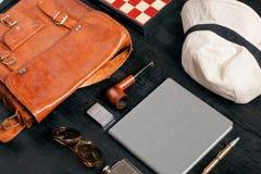 Selektiv fokus på olika objekt för loppet och ferie av en man - solglasögon, anteckningsbok, påse, hatt, rör, schackbräde Royaltyfri Bild