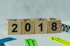 Selektiv fokus på träkubkvarteret med numret 2018 med pilen Arkivbilder