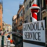 Selektiv fokus på traditionella röda och vita poler som annonserar gondolservice i Venedig arkivbild