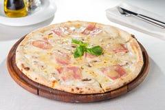 Selektiver Fokus Abschluss herauf köstliche Pizza mit der Pilze in Scheiben und Frischkäse des Speckes, auf dem hölzernen Brett a Stockfotografie