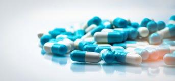 Selektiver Fokus auf Blauer und Weißkapselpille verbreitete auf weißem Hintergrund mit Schatten globales Gesundheitswesenkonzept  Lizenzfreie Stockfotos