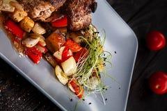 Selektiver Fokus auf gedientem Fleisch auf dunklem Hintergrund lizenzfreie stockfotografie