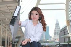 Selektiver Fokus auf Gesicht attraktiver junger asiatischer Sekretärfrau, die Dokumentenordner hält und im äußeren Büro lächelt stockfotografie