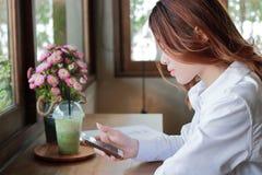 Selektiver Fokus auf Gesicht der attraktiven jungen asiatischen Geschäftsfrau, die intelligentes Mobiltelefon in ihren Händen zwi Lizenzfreies Stockfoto