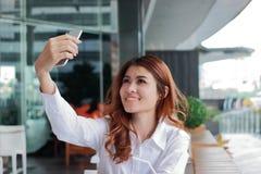 Selektiver Fokus auf Händen der attraktiven jungen Asiatin, die Foto oder selfie am intelligenten Mobiltelefon im Büro nimmt Flac Lizenzfreie Stockfotografie