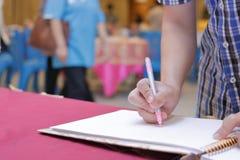 Selektiver Fokus auf Händen des jungen Gastmannschreibens auf Gedächtnisbuch für die Segnung des Wortes, um sich zu pflegen und d Stockbild