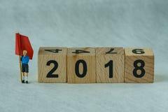 Selektiver Fokus auf Holzklotz 2018 mit Miniaturzahl Mann-Stunde Stockfoto
