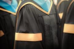 Selektiver Fokus auf Kleidern des Hochschulabschlusses graduiert im commenc Lizenzfreie Stockbilder