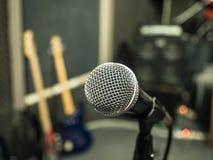 Selektiver Fokus auf Mikrofon mit undeutlichem Musikstudiohintergrund Lizenzfreies Stockfoto