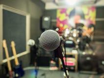 Selektiver Fokus auf Mikrofon mit undeutlichem Musikstudiohintergrund Lizenzfreie Stockfotos