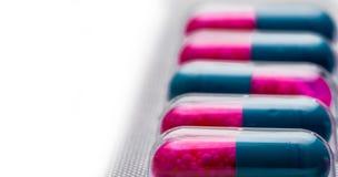 Selektiver Fokus der blauen, rosa Kapsel mit Körnchen in den Seitenpillen Pillen in der Blisterpackung auf weißem Hintergrund Pha Stockfotografie