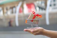 Selektiver Fokus der Frau übergibt das Halten der Geschenkbox mit rotem Band lizenzfreies stockbild