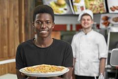 Selektiver Fokus des erfüllten Kunden köstliche Pizza halten stockfotografie