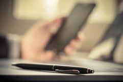Selektiver Fokus sperrt Lügen in der Laptoptastatur auf Hintergrundgeschäftsmann unter Verwendung eines undeutlichen Handys ein Lizenzfreie Stockbilder