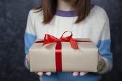 Selektiver Fokus von den Frauenhänden, die Geschenkbox mit rotem Band für Weihnachten und Neujahrstag halten oder Jahreszeit grüß lizenzfreie stockbilder