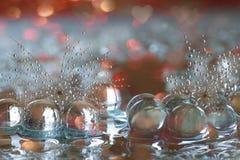 Selektiver Fokus von Glasperlen und von Löwenzahnsamen auf einer Spiegel-reflektierenden Oberfläche Stockbilder