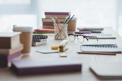 selektiver Fokus von pädagogischen Schreibheften, von Büchern, von Bleistiften und von Brillen Stockbild
