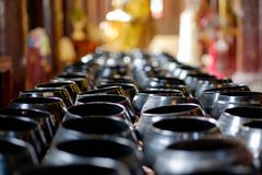 Selektiver Fokus von Schüsseln mit Münze im Buddhismustempel Lizenzfreies Stockfoto
