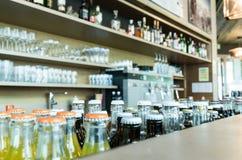 Selektiver Fokus von viele Getränke und Getränke auf und hinter einer stilvollen Bar und einem Aufenthaltsraum mit Kaffeemaschine stockbild