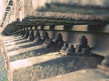Selektivt fält av fokusen Detalj av rostiga skruvar och muttern på gammalt järnvägspår Konkret band Royaltyfri Bild