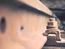 Selektivt fält av fokusen Detalj av rostiga skruvar och muttern på gammalt järnvägspår Konkret band Royaltyfria Bilder