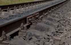 Selektivt fält av fokusen Detalj av rostiga skruvar och muttern på gammalt järnvägspår Konkret band med rostiga muttrar - och - b Royaltyfri Fotografi