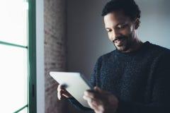 Selektivt fokusera Le läs- nyheterna för skäggig afrikansk man digital minnestavla, medan stå nära fönstret i hans modernt royaltyfri fotografi