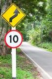 Selektivt hastighetsbegränsningtrafiktecken 10 och varningssymbol för slingrig väg för säkerhetsdrev i landsväg i skog för bergsi Arkivbilder