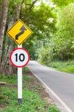 Selektivt hastighetsbegränsningtrafiktecken 10 och varningssymbol för slingrig väg för säkerhetsdrev i landsväg i skog för bergsi Arkivbild