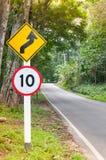 Selektivt hastighetsbegränsningtrafiktecken 10 och varningssymbol för slingrig väg för säkerhetsdrev i landsväg i skog för bergsi Fotografering för Bildbyråer