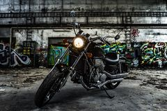 Selettore rotante del motociclo in un vecchio corridoio industriale con i graffiti urbani fotografia stock libera da diritti