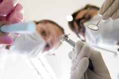 Selezionamento e specchio della holding dell'assistente e del dentista Fotografie Stock Libere da Diritti