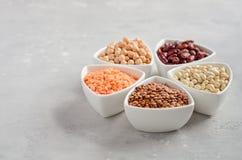 Selezione dei legumi, delle lenticchie e dei piselli asciutti in ciotole bianche su fondo concreto grigio Immagine Stock