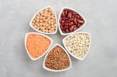 Selezione dei legumi, delle lenticchie e dei piselli asciutti in ciotole bianche su fondo concreto grigio Fotografia Stock Libera da Diritti