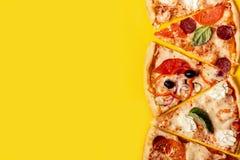 Selezione della pizza assortita dei pezzi su fondo giallo Pizza delle merguez, del vegetariano e dei frutti di mare immagine stock