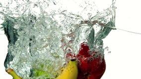 Selezione di frutta che si tuffa in acqua su fondo bianco archivi video