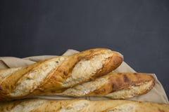 Selezione fatta a mano del pane francese su fondo nero con area della copia fotografia stock