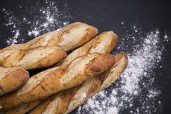 Selezione fatta a mano del pane francese su fondo nero con area della copia immagine stock
