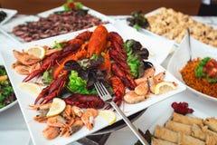 Selezione fine del crostaceo per la cena Aragosta, granchio e gamberetto enorme su un piatto bianco Immagini Stock