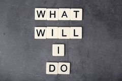An abstract question What will I do formed with letter tiles. A self-asking question about your plans and goals formed with plastic letters royalty free stock images