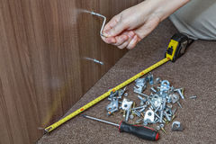 Self-assembly furniture, hand with an Allen key tighten screw. Stock Image