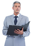 Self assured businessman with clipboard Stock Photo