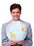 Self-assured businessman holding a globe Royalty Free Stock Photos