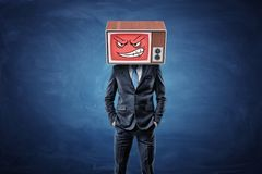 A self-assured businessman holds his hands in pockets and wears an old TV with an angry smiley face on his head. New personality. Be more aggressive Royalty Free Stock Photo