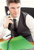 Self-assured businessman on phone using his laptop Stock Images